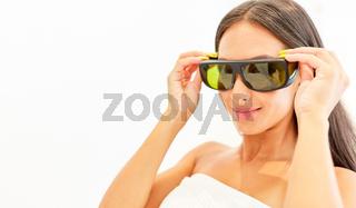 Junge Frau setzt sich eine Schutzbrille auf