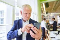 Geschäftsmann schreibt eine SMS auf dem Smartphone
