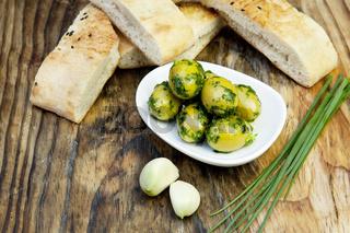 Grüne Oliven mit frischem Brot und Kräutern auf einem Holzbrett