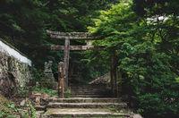 Old stone torri gate over a stairs path in park on Mount Misen in Miyajima, Hiroshima, Japan
