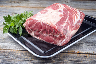 Traditional raw corned pot pork roast with herbs offer offered as close-up on a rustic metal tray at a chalet