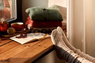 feet in warm socks on windowsill at home in autumn
