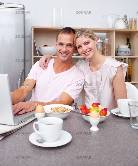 Affectionate couple using a laptop while having breakfast
