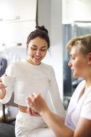 Beautician applying cream on hands of woman in salon