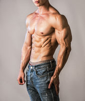 Unrecognizable young man with naked muscular torso, wearing jeans
