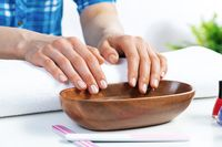 Closeup female hands in wooden bowl with water