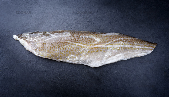 Raw Norwegian skrei cod fish filet with skin offered as top view on black board with copy space