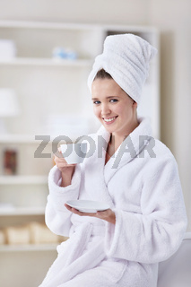 A beautiful young girl in a bathrobe and a towel with a cup of coffee