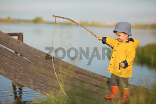 Little Boy Catching a Fish from wooden dock