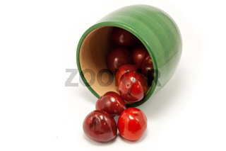 Juicy ruby red cherries in a green cup