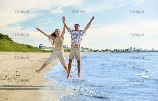 happy couple jumping on summer beach