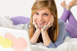 Young girl lying on bed with laptop