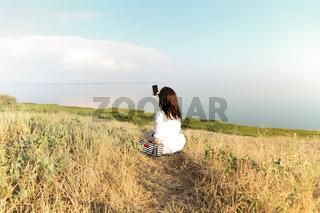 Woman taking selfie on smartphone on hill