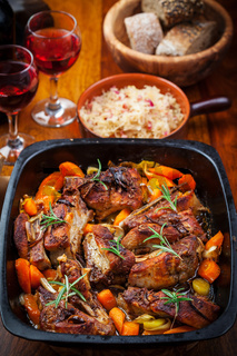 Roasted pork belly on vegetables  with sauerkraut and red wine