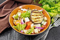 Salad of eggplant with feta and tomatoes on board