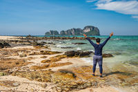 Tropical islands view with man tourist looking at ocean blue sea water and white sand beach at Bamboo Island, Krabi Thailand nature landscape