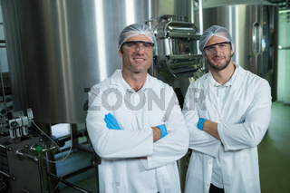 Portrait of scientists standing by storage tank in warehouse