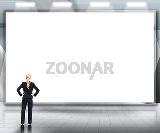 Businesswoman looking up at large blank screen under spotlights
