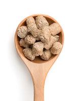 Top view of oats bran pellets in wooden spoon