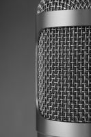 Closeup of a gray microphone on gray background