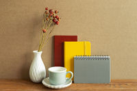 Notebook, coffee cup, dry flower on wooden desk. brown wall background. Workspace