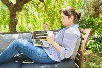 Frau am Laptop Computer in der Natur im Garten
