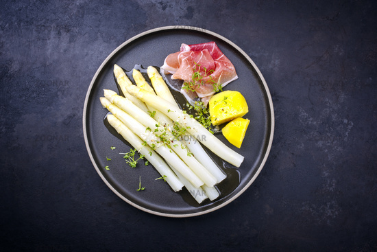 Traditional steamed white asparagus with cured ham and boiled potatoes garnished with butter sauce served as top view on a Nordic design plate