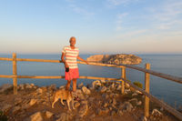 Man with dog in front of landscape with Les Medes islands