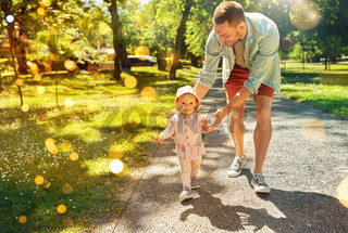 happy father with baby daughter walking at park