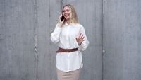Cheerful businesswoman speaking on smartphone on street