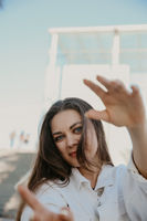 Vertical shot of young woman, wears white clothing. Lifestyle concept.