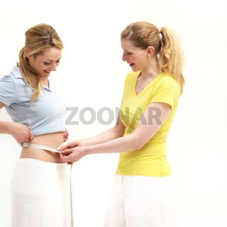 Woman measuring her friends waist