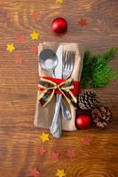 Composition of christmas decorations with cutlery and napkin on wooden background