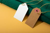 Composition of gift tags with copy space and green fabric on yellow background