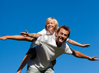 Happy father with his son on his back outdoor