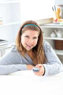 Charming young woman holding a  remote sitting in the kitchen