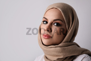 Close-up portrait of young muslim woman wearing beige hijab. Space for text.
