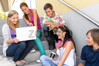 Students having fun with laptop school stairs