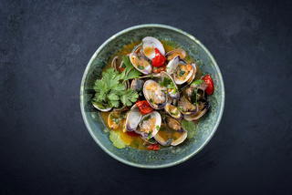 Modern style traditional Italian venus clams soup with tomatoes and garlic in a wine jus as top view in a Nordic design bowl