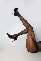 Vertical image of female legs with high heels shoes. Isolated over white wall.