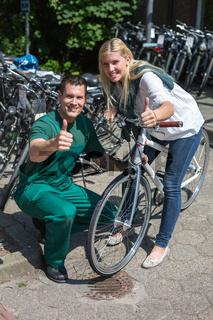 Fahrradmechaniker berät Kundin in Fahrradladen