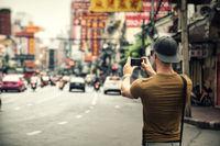 Man taking photo of city on smartphone