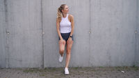 Optimistic female athlete taking break near wall