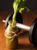 Healthy vegetable fruit smoothie from organic ingredients with dumbbells