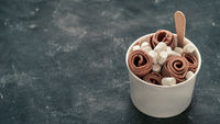 Rolled ice cream in cone cup on dark,copy space
