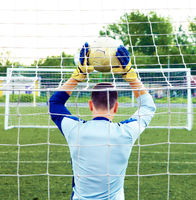 Soccer goalkeeper trying to defend grass football field with ball and gate  Copy space for inscription