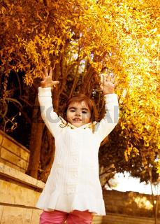 Small girl in autumn backyard