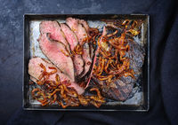 Traditional Commonwealth Sunday roast with sliced cold cuts roast beef with fried onion rings served as top view on an old rustic metal tray