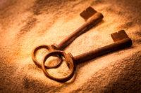 Two old rusty keys in sand in warm tones