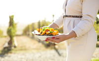Cropped photo of unknown female holding snack plate with quinoa and yellow pumpkin dish outside
